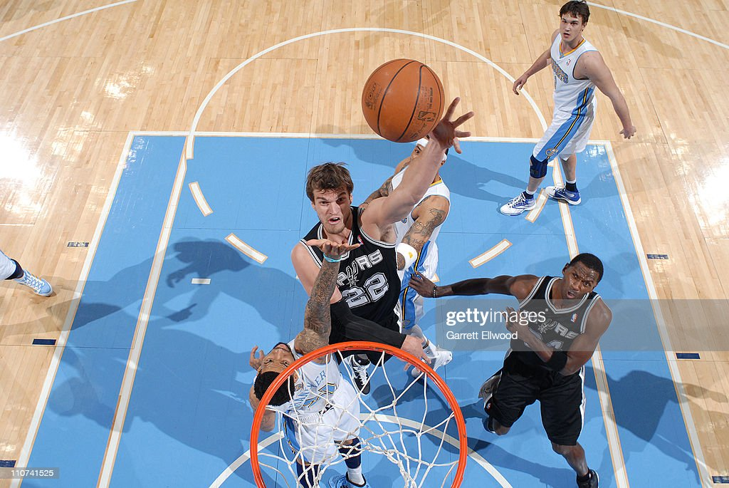<a gi-track='captionPersonalityLinkClicked' href=/galleries/search?phrase=Tiago+Splitter&family=editorial&specificpeople=208218 ng-click='$event.stopPropagation()'>Tiago Splitter</a> #22 of the San Antonio Spurs takes a shot against <a gi-track='captionPersonalityLinkClicked' href=/galleries/search?phrase=Wilson+Chandler&family=editorial&specificpeople=809324 ng-click='$event.stopPropagation()'>Wilson Chandler</a> #21 of the Denver Nuggets on March 23, 2011 at the Pepsi Center in Denver, Colorado.