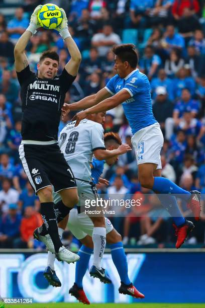 Tiago Volpi of Queretaro jumps to catch the ball against Angel Mena of Cruz Azul during the 5th round match between Cruz Azul and Queretaro as part...