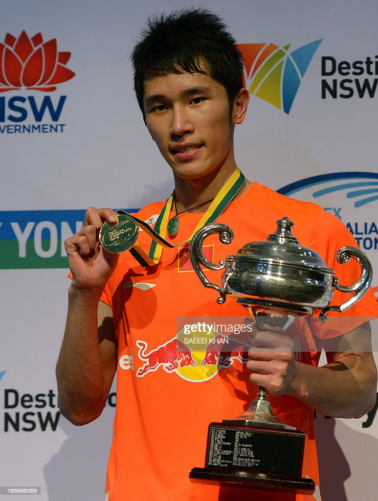 Tian Houwei of China lifts the winner s trophy after defeating Xue