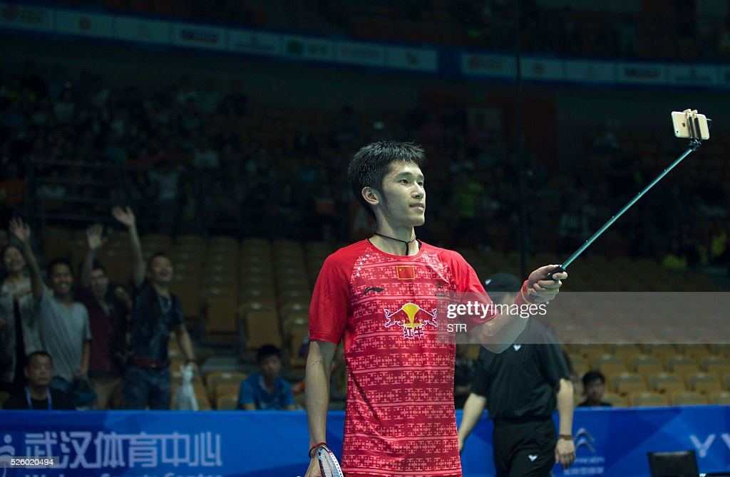 Tian Houwei (R) of China uses selfie sticks to take photos with fans after winning the men's singles quarter-final match against Tzu Wei Wang of Taipei at the 2016 Badminton Asia Championships in Wuhan, central China's Hubei province on April 29, 2016. / AFP / STR