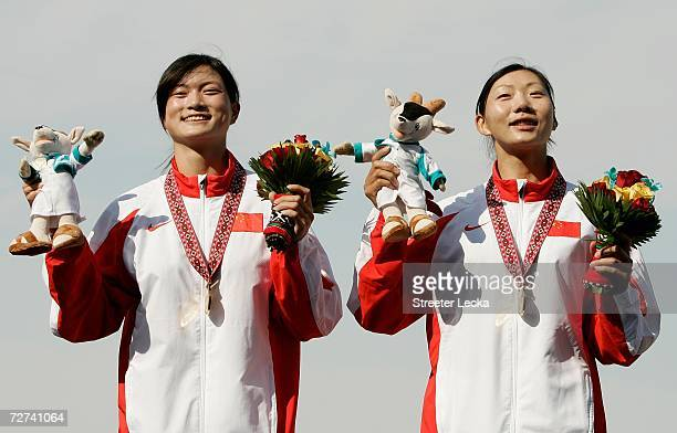 Tian Liang and Li Qin of Team China celenbrate on the podium after winning the Gold Medal in the Women's Double Sculls Rowing Competition during the...