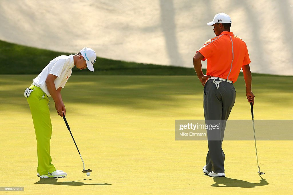 Tianlang Guan of China putts as Tiger Woods of the United States look on during a practice round prior to the start of the 2013 Masters Tournament at Augusta National Golf Club on April 8, 2013 in Augusta, Georgia.
