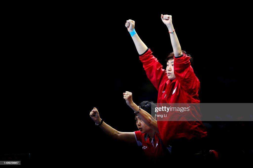Tianwei Feng (R) of Singapore and head coach Jing Junhong (L) cheer for teammates Yuegu Wang and Jiawei Li of Singapore as they take on Yeseo Dang and Hajung Seok of Korea during the Women's Team Table Tennis bronze medal match on Day 11 of the London 2012 Olympic Games at ExCeL on August 7, 2012 in London, England.