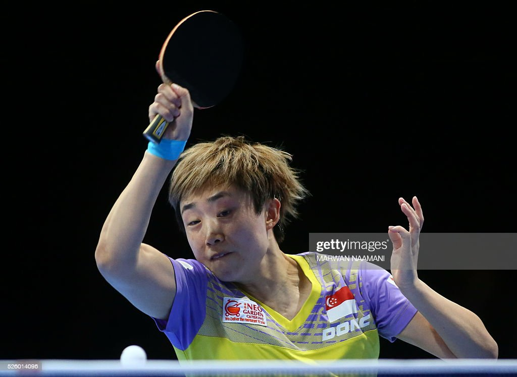 Tianwei Feng of Singapore returns the ball to Xiaoxia Li of China during their women's singles semi final table tennis match in the ITTF Nakheel Table Tennis Asian Cup, on April 29, 2016 in Dubai.. / AFP / MARWAN