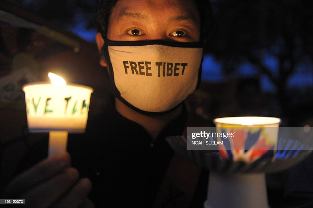 A Tibetan activist holds a candle as members of the Regional Tibetan Youth Congress (RTYC) take part in a candlelight vigil during protest rally in Hyderabad on March 10, 2013.The protest marked the 54th anniversary of the Tibetan national uprising, the 1959 rebellion against China's rule in Tibet. AFP PHOTO/ Noah SEELAM