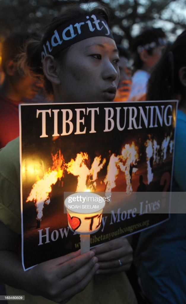 A Tibetan activist holds a candle as other members of the Regional Tibetan Youth Congress (RTYC) take part in a candlelight vigil during protest rally in Hyderabad on March 10, 2013.The protest marked the 54th anniversary of the Tibetan national uprising, the 1959 rebellion against China's rule in Tibet. AFP PHOTO/ Noah SEELAM