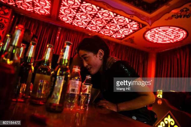 A Tibetan bar girl talks to a guest in Tibetan Bar on July 22 2017 in Litang County southwest of Garze Tibetan Autonomous Prefecture Sichuan China...