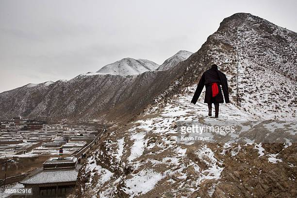Tibetan Buddhist man wears a traditional jacket as he walks on a hillside during Monlam or the Great Prayer rituals on March 4 2015 overlooking the...