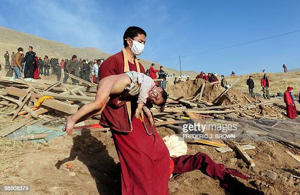 Tibetan Buddhist monk carries the body of a child earthquake victim towards a mass cremation on a hillside in Jiegu Yushu County on April 17 2010...
