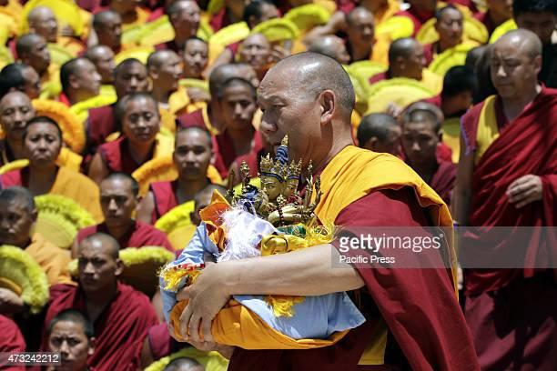 Tibetan Buddhist monk carrying idol during the teaching by Tibetan spiritual leader the Dalai Lama at Gyuto Monastery on last day of religious talk...