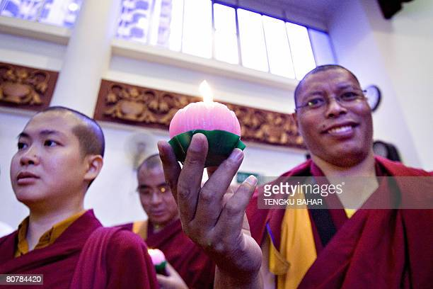 A Tibetan Buddhist monk holds up a lotus candle during a multifaith prayer session calling for peace in Tibet following recent riots and a safe...