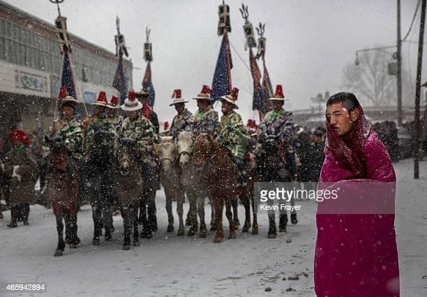 Tibetan Buddhist monk of the Gelug or Yellow Hat order looks on as horseman take part in a procession during Monlam or the Great Prayer rituals on...