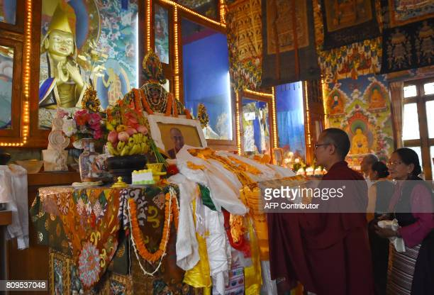 A Tibetan Buddhist monk performs rituals in front of a portrait of spiritual leader the Dalai Lama during events to mark his birthday at Boudhanath...
