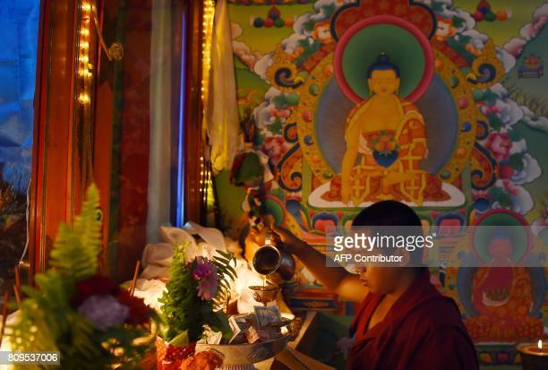 A Tibetan Buddhist monk performs rituals to mark the birthday of spiritual leader the Dalai Lama at Boudhanath Stupa in the Nepalese capital...