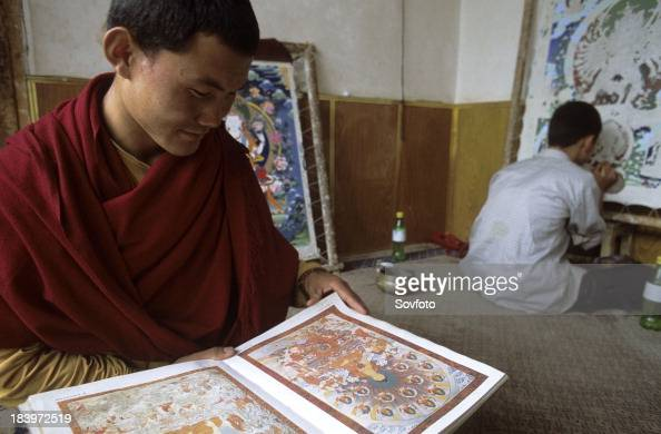 Tibetan Buddhist monk sitting while holding a book with examples of thangka's beside him a man is painting a thangka Tongren Qinghai Province China...