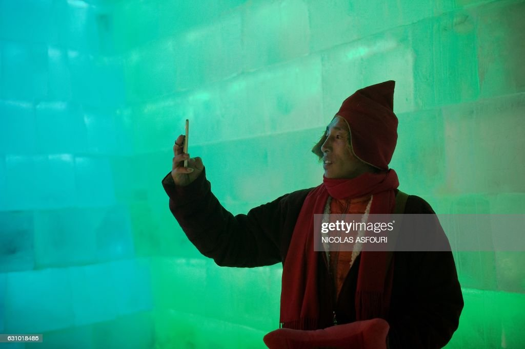A Tibetan Buddhist monk takes a photo with his smartphone as he visits ice sculptures illuminated by coloured lights at the Harbin Ice and Snow Festival to celebrate the new year in Harbin on January 5, 2017. / AFP / Nicolas ASFOURI