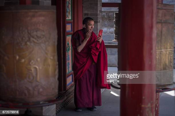 Tibetan buddhist monk use iphone in the courtyard of the Kumbum Monastery on April 23 2017 in Xining Qinghai Province Kumbum was founded in 1583 in a...