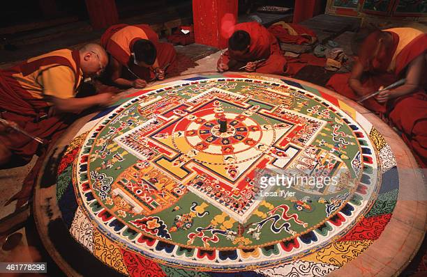 Tibetan Buddhist monks design a sand mandala in Litang Gompa They pour coloured sands into the design resembling the Wheel of Life a diagram that...