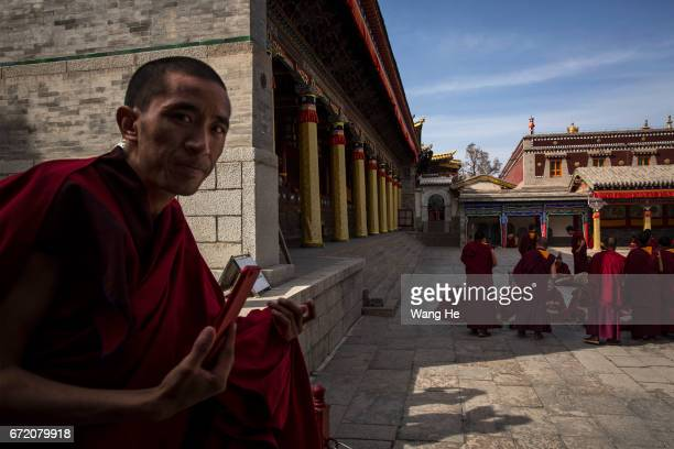 Tibetan Buddhist monks during a debate about Buddhist related issues as Tibetan Buddhist monks use iphone in the courtyard of the Kumbum Monastery on...
