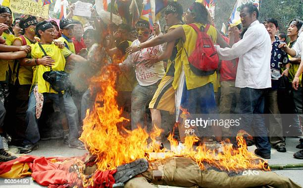 Tibetan Buddhist monks in exile and demonstrators shout anti Chinese slogans as they burn effigies of Chinese Premier Hu Jintao and Chinese flagsat...