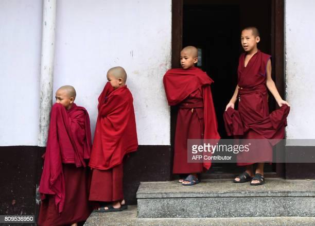 Tibetan Buddhist monks look on during events to mark the birthday of spiritual leader the Dalai Lama at Boudhanath Stupa in Kathmandu on July 6 2017...