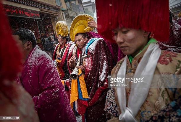 Tibetan Buddhist monks of the Gelug or Yellow Hat order are covered in snow as they take part in a procession during Monlam or the Great Prayer...