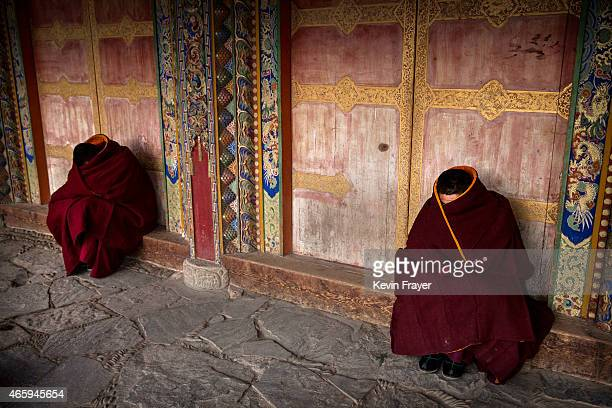 Tibetan Buddhist Monks of the Gelug or Yellow Hat order rest on a cold morning outside prayers during Monlam or the Great Prayer rituals on March 3...