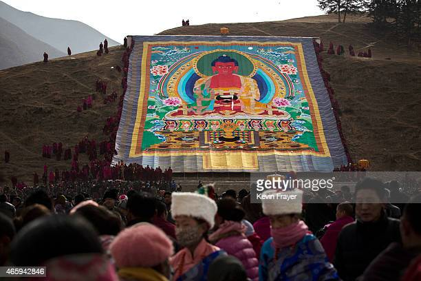 Tibetan Buddhist Monks of the Gelug or Yellow Hat order unveil a large thangka showing Buddha during Monlam or the Great Prayer rituals on March 3...