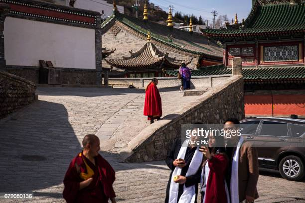 Tibetan buddhist monks walk as tourists poses take pictures in the courtyard of the Kumbum Monastery on April 23 2017 in Xining Qinghai Province...