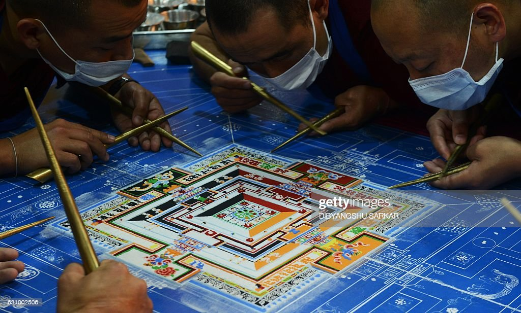 Tibetan Buddhist monks work on a traditional painting during a special religious prayer during the Kalachakra event at Bodhgaya on January 5, 2017. / AFP / Dibyangshu SARKAR