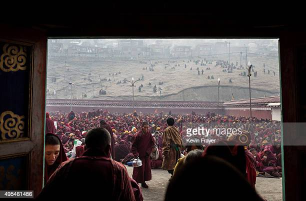 Tibetan Buddhist nuns carry tea as others sit during a morning chanting session at the annual Bliss Dharma Assembly at the Larung Wuming Buddhist...
