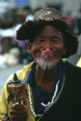 Tibetan Buddhist touches his nose with the tip of his tongue in a traditional Tibetan greeting while circumambulating the Jokhang Temple in Lhasa He...