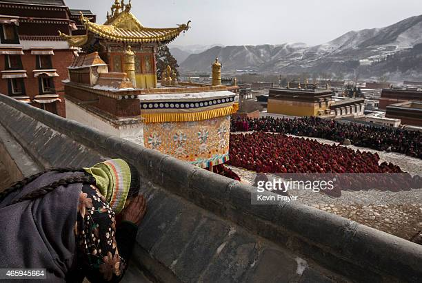 Tibetan Buddhist woman bows her head in prayer as monks take part in a special prayer during Monlam or the Great Prayer rituals on March 5 2015 at...