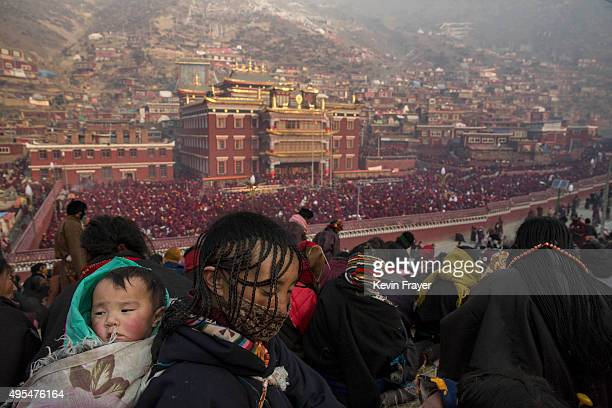 Tibetan Buddhist woman carries her son in the crowd on a hillside overlooking a chanting session at the annual Bliss Dharma Assembly at the Larung...