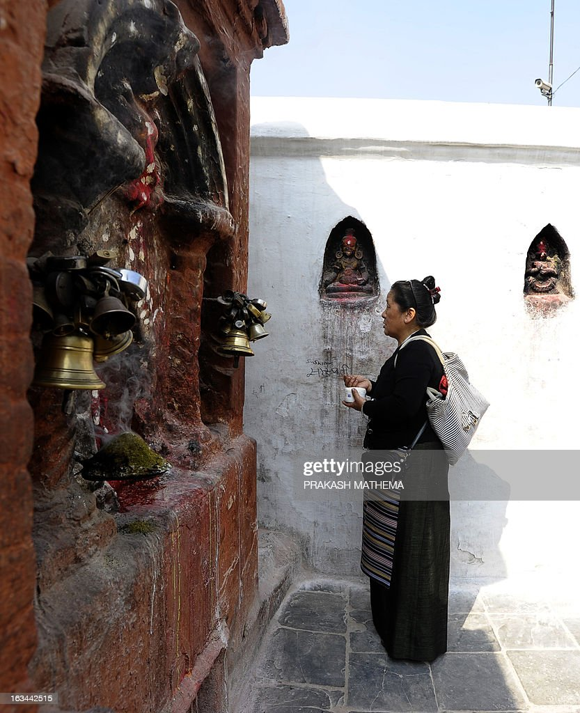 A Tibetan Buddhist woman prays at the Bouddhanath Stupa during the 54th anniversary of the 1959 Tibetan uprising against Chinese rule, in Kathmandu on March 10, 2013. Nepalese police arrested 11 people in Kathmandu on suspicion of 'anti-China activities' on Sunday morning, the anniversary of the 1959 rebellion against China's rule in Tibet. AFP PHOTO/Prakash MATHEMA