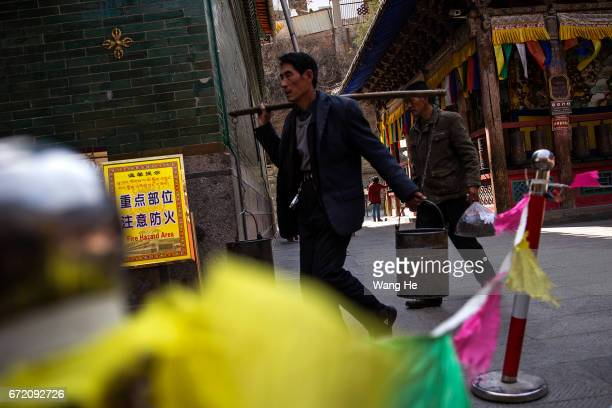 A Tibetan buddhist worshipper carries water with a carrying pole as a tourist poses in the courtyard of the Kumbum Monastery on April 23 2017 in...