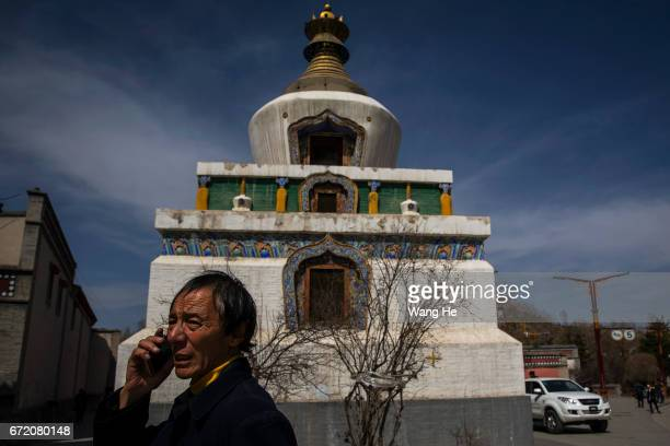 Tibetan buddhist worshipper make call in the courtyard of the Kumbum Monastery on April 23 2017 in Xining Qinghai Province Kumbum was founded in 1583...