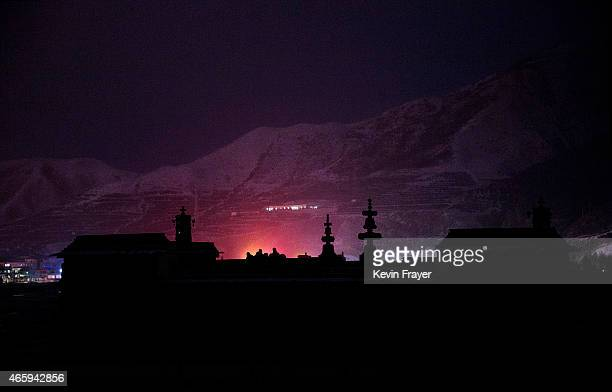 Tibetan Buddhists monks pray on a rooftop during Monlam or the Great Prayer rituals on March 4 2015 at the Labrang Monastery Xiahe County Amdo...
