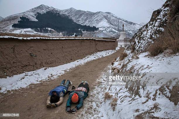 Tibetan Buddhists prostrate themselves as they perform Kora during a pilgrimage for Monlam or the Great Prayer rituals on March 4 2015 at the Labrang...
