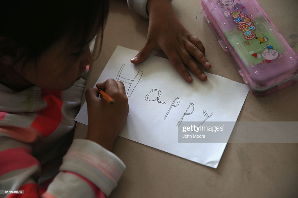 A Tibetan child draws during an after-school program for asylum immigrants run by the International Rescue Committee (IRC), on April 25, 2013 in the Queens borough of New York City. The after-school program held at P.S. 199 consists of homework help and visual art instruction for Tibetan children in grades 2 through 4. The IRC is a non-profit humanitarian aid organization that aids refugees and survivors of international conflict. They assist new arrivals, many of whom come from refugee camps and war zones, to adjust to American society after being granted refugee status and invited by the U.S. government to live in the United States. The IRC also assists refugees through the immigration and naturalization process to become U.S. citizens.