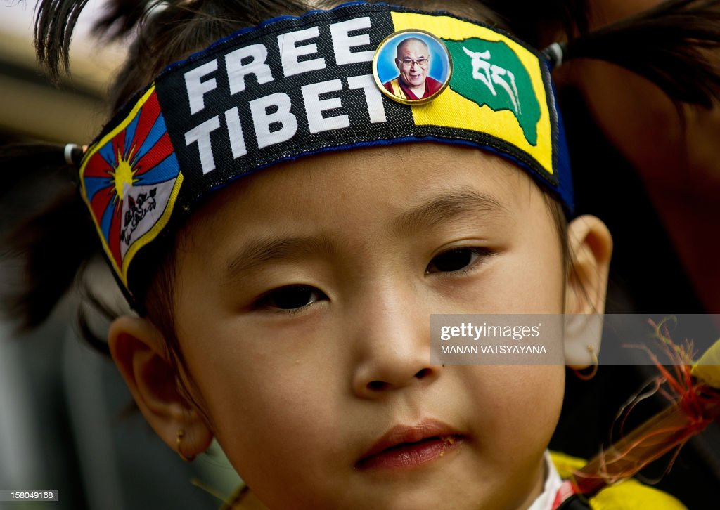 A Tibetan child is pictured with a Free Tiet bandana as Tibetan activists in-exile take part in a protest in New Delhi on December 10, 2012 to mark World Human Rights Day. A 16-year-old Tibetan girl has died after setting herself on fire, Chinese state media said December 10, in an area that has become a flashpoint for protests against Beijing's rule. AFP PHOTO/MANAN VATSYAYANA