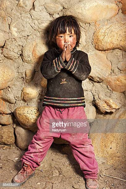 Tibetan child standing in front of the house. Mustang, Nepal.