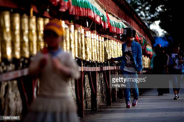 Tibetan children turn the prayer wheels near by the Potala Palace on August 19 2012 in Lhasa China Lhasa is the administrative capital of the Tibet...