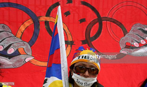 A Tibetan demonstrator is seen near a flag representing the Beijing Olympics during a protest in Siliguri on March 18 2008 Tibet remained largely cut...