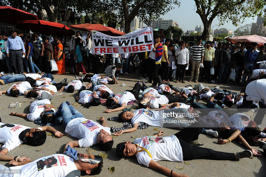 Tibetan exiles residing in India lie on a road during a protest rally in New Delhi on March 10, 2013. The protest marked the 54th anniversary of the Tibetan national uprising, the 1959 rebellion against China's rule in Tibet. AFP PHOTO/ Sajjad Hussain