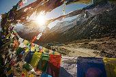 Tibetan Flags on Annapurna Base Camp in Nepal, Himalaya. Sunrise above Machapuchare mountain