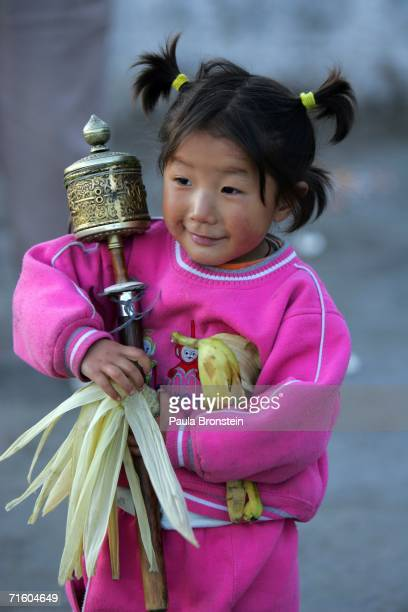 Tibetan girl holds her grandmother's prayer wheel in front of the Jokhang temple August 6 2006 in Lhasa in the Tibet Autonomous Region China Lhasa's...