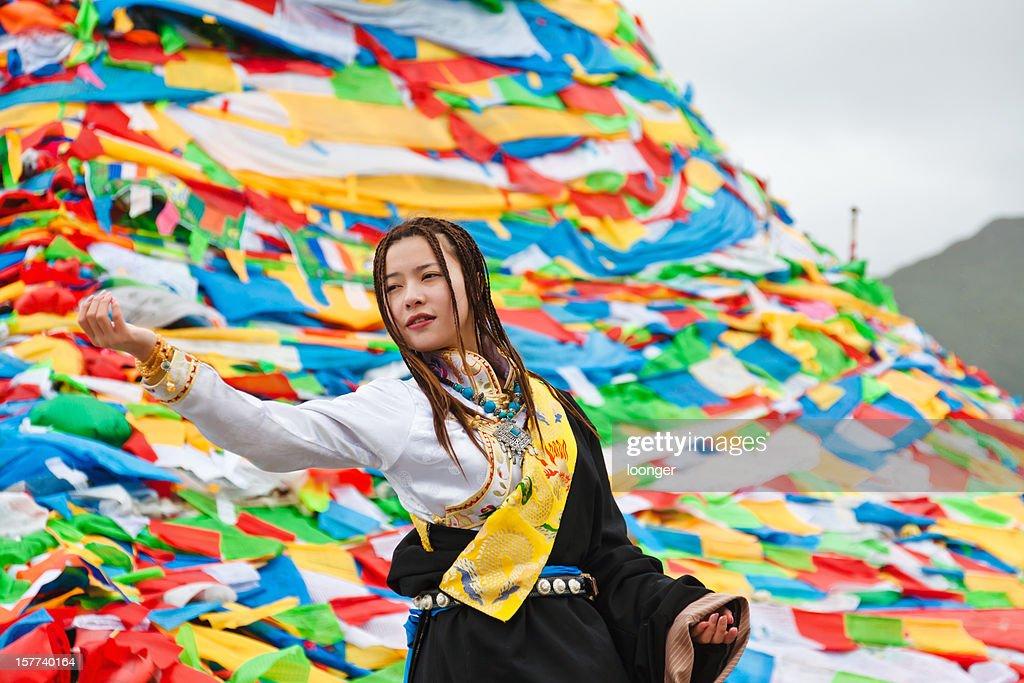 tibetan girl praying before the prayer flags