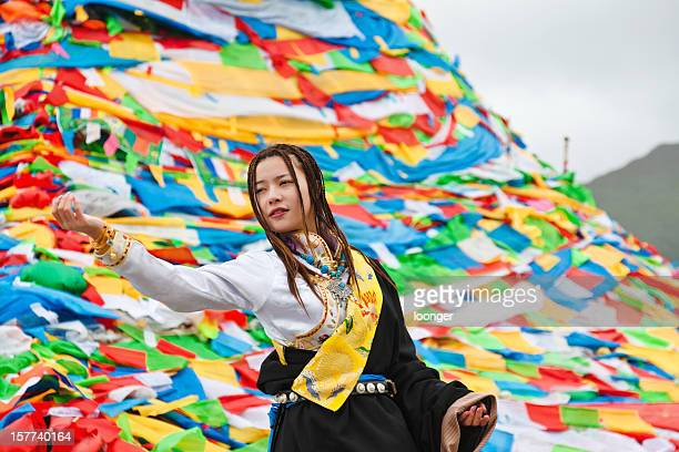 tibetan girl praying before the prayer flags