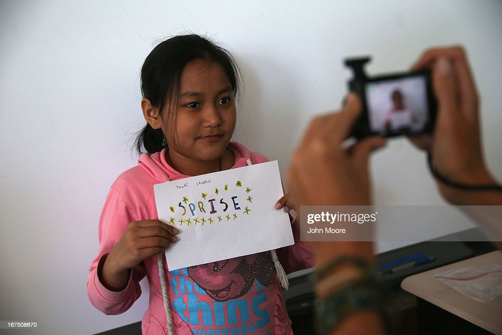 A Tibetan immigrant child displays her artwork during an after-school program for asylum immigrants run by the International Rescue Committee (IRC), on April 25, 2013 in the Queens borough of New York City. The after-school program held at P.S. 199 consists of homework help and visual art instruction for Tibetan children in grades 2 through 4. The IRC is a non-profit humanitarian aid organization that aids refugees and survivors of international conflict. They assist new arrivals, many of whom come from refugee camps and war zones, to adjust to American society after being granted refugee status and invited by the U.S. government to live in the United States. The IRC also assists refugees through the immigration and naturalization process to become U.S. citizens.